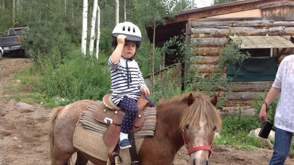 A little kid riding a pony at Vail Stables