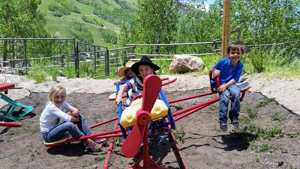 Three kids playing on a seesaw at Vail Stables
